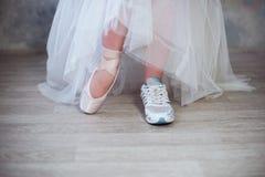 Les jambes d'une ballerine, un pied ont chaussé dans des espadrilles autre dans des chaussures de pointe Image stock