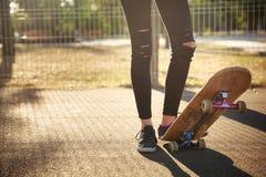 Les jambes d'une fille de planchiste dans des espadrilles font un tour sur une planche à roulettes Photos libres de droits