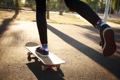 Les jambes d'une fille de planchiste dans des espadrilles font un tour sur une planche à roulettes Images libres de droits