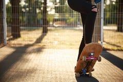 Les jambes d'une fille de planchiste dans des espadrilles font un tour sur une planche à roulettes Photographie stock