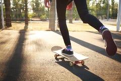 Les jambes d'une fille de planchiste dans des espadrilles font un tour sur une planche à roulettes Images stock