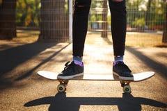 Les jambes d'une fille de planchiste dans des espadrilles font un tour sur une planche à roulettes Image libre de droits