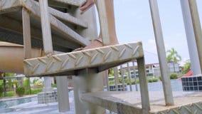 Les jambes d'une jeune femme en sandales, montent l'escalier en spirale blanc banque de vidéos