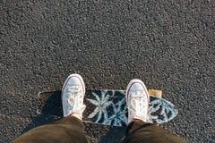 Les jambes dans des espadrilles blanches sur un patin embarquent Photo stock