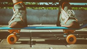 les jambes dans des espadrilles de vintage se tiennent sur une planche à roulettes Un planchiste se repose sur un banc en parc, u Image libre de droits