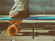 les jambes dans des espadrilles de vintage se tiennent sur une planche à roulettes Un planchiste se repose sur un banc en parc, u Image stock