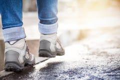 Les jambes dans des espadrilles vont sur une restriction humide le long du trottoir Ressort nous Photographie stock libre de droits