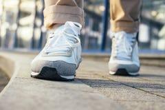 Les jambes dans le pantalon beige et des espadrilles blanches sont sur le trottoir Images libres de droits