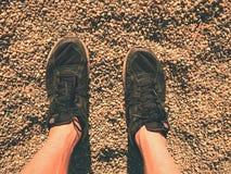 Les jambes dans le sport noir chausse la marche sur la terre arénacée Jambes de peau velue d'homme dans des chaussures noires Image stock
