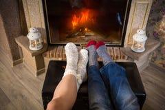 Les jambes dans les chaussettes de laine réchauffent près de la cheminée, au-dessus de la vue Photos stock