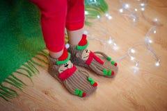 Les jambes dans les chaussettes s'approchent de la guirlande de Noël Photo stock