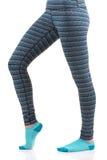 Les jambes de femme dans le pantalon thermique et les chaussettes bleues de la vue de côté se tenant sur une jambe avec autre se  Image stock