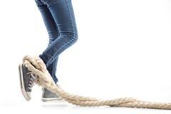 Les jambes de femme dans les jeans et des espadrilles ont empêtré la corde sur le fond blanc Concept des restrictions Image stock