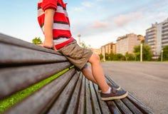 Les jambes de garçon se reposant sur le dessus du banc garent la détente Images libres de droits