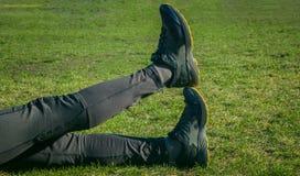 Les jambes de l'athlète dans les guêtres et des espadrilles, se trouvant au sol sur le plan rapproché de pelouse Pattes crois?es  photographie stock