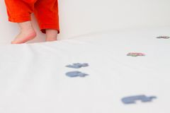 Les jambes de l'enfant, qui se tient sur le lit Photos libres de droits