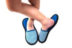 Les jambes de l'enfant se tenant avec les chaussures molles faites main d'intérieur Photographie stock libre de droits