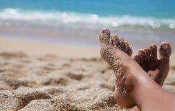 Les jambes de la femme à la plage Images stock