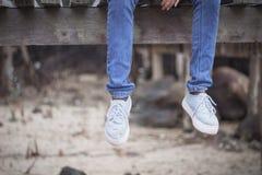 Les jambes de la femme accrochant sur le vieux pont en bois Le style isolé de vintage de ton n'aiment pas autre Images stock