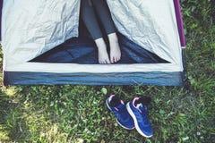 Les jambes de la femme dans la tente ouverte et des ses espadrilles de sport sur l'herbe Photo stock
