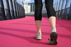 Les jambes de la femme marchant sur une route rose lumineuse Photos libres de droits
