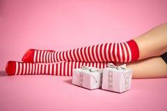 les jambes de la femme de Santa sur un fond rose et des cadeaux de Noël image stock