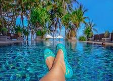 Les jambes de la femme se couchant sur une chaise longue regardant au-dessus de l'eau Photos stock