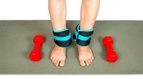 Les jambes de la fille avec des poids et des haltères de cheville, d'isolement Photo stock