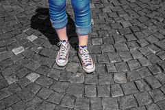 Les jambes de la fille dans des chaussures en caoutchouc sur le trottoir Images libres de droits