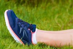 Les jambes de la fille dans les espadrilles se trouvent sur l'herbe verte Repos après des sports Concept d'un mode de vie et d'un Image stock