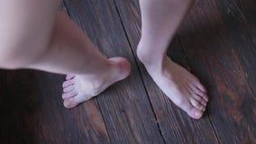 Les jambes de la fille sur un plancher en bois banque de vidéos