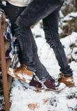 Les jambes de la jeune fille se tiennent vis-à-vis des jambes du jeune homme, amants Fond de neige Chaussures de mode et jeans gr Images libres de droits