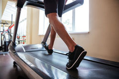 Les jambes de la jeune forme physique équipent le fonctionnement sur le tapis roulant dans le gymnase photos libres de droits