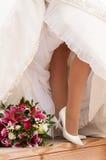Les jambes de la jeune mariée avec le boquet Image stock