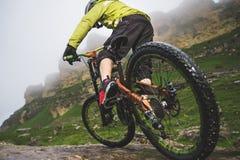 Les jambes de la vue en gros plan de cycliste et de roue arrière du mtb arrière font du vélo en montagnes sur le fond des roches  images stock