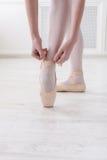 Les jambes de plan rapproché de la ballerine met dessus des chaussures de ballet de pointe Photos libres de droits
