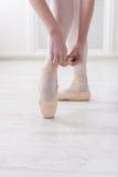 Les jambes de plan rapproché de la ballerine met dessus des chaussures de ballet de pointe Photographie stock libre de droits