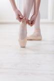 Les jambes de plan rapproché de la ballerine met dessus des chaussures de ballet de pointe Photographie stock