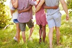 Les jambes de quatre amis marchant ensemble dans la campagne Image stock