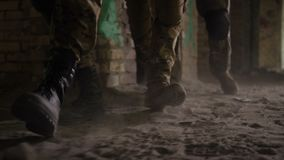 Les jambes de soldat dans des bottes de combat d'armée marchent dans le bâtiment banque de vidéos