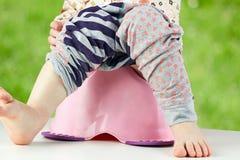 Les jambes des enfants pendant vers le bas d'un chambre-pot Images stock