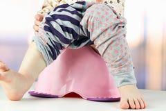 Les jambes des enfants pendant vers le bas d'un chambre-pot Photographie stock