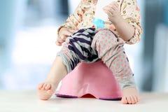 Les jambes des enfants pendant vers le bas d'un chambre-pot sur un backgr bleu Image libre de droits