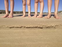 Les jambes des enfants sur la plage Image stock