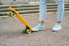 Les jambes des femmes dans les jeans et des espadrilles se tenant à côté du patin Photographie stock libre de droits