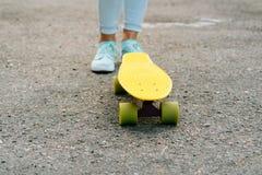 Les jambes des femmes dans les jeans et des espadrilles se tenant près du skateboa jaune Photo libre de droits