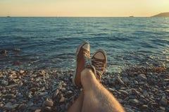 Les jambes des hommes dans des espadrilles à l'arrière-plan de la mer pittoresque aménagent le concept en parc de détente de plag Images stock