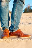 Les jambes des hommes dans les jeans et des chaussures de luxe élégantes en cuir brunes Image libre de droits