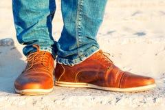 Les jambes des hommes dans les jeans et des chaussures de luxe élégantes en cuir brunes Photos stock