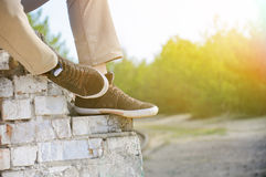 Les jambes des hommes dans le brun chausse des espadrilles Photographie stock